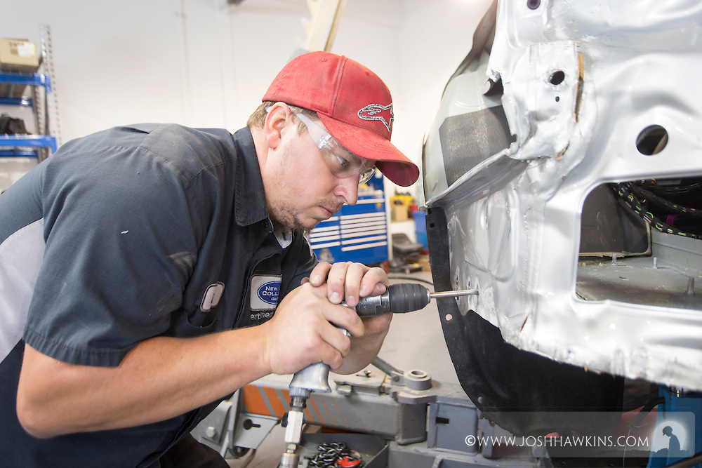 Brock Burton working on a car on a special Audi lift. <br /> <br /> JH_201510021104_MG_5974.CR2<br /> 10/2/2015  --  11:04:52
