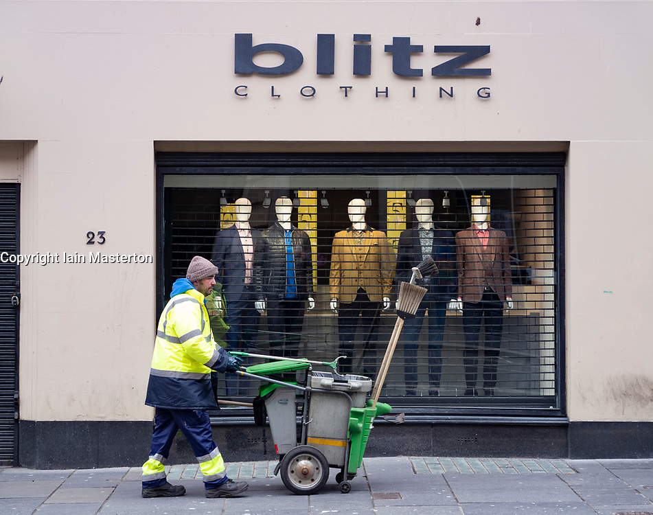 Glasgow, Scotland, UK. 26 March, 2020. Views from city centre in Glasgow on Thursday during the third day of the Government sanctioned Covid-19 lockdown. The city is largely deserted. Only food and convenience stores open. Street cleaner , an essential worker, walks past closed mens fashion store. Pictured; Iain Masterton/Alamy Live News