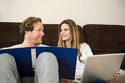 Couple with documents and laptop in living room