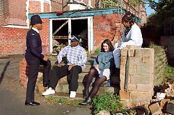 Teenagers sitting on steps on street corner talking with community policeman,