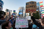"""President Donald Trump appears as a news item on big screens as a woman holds a  sign reading """"will trade President for Refugees"""" at the Vote Out the Scandal rally at Hachiko Square, Shibuya, Tokyo, Japan. Sunday November 5th 2017. Timed to coincide with President Trumps visit to Japan, About 120 Americans living in Japan and some local Japanese  protested together from 2pm to 4pm to encourage US citizens to register to vote in future elections and call on the US government to honour it responsibilities to the American people,."""