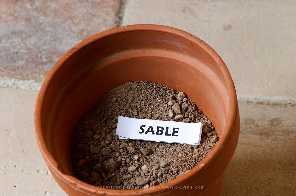 Plant pot with soil sample to illustrate different soil types, part of a series: sand, sable. Chateau Villerambert-Julien near Caunes-Minervois. Minervois. Languedoc. Terroir soil. France. Europe. Sand.