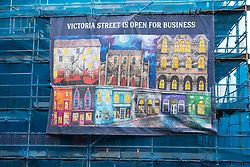 Edinburgh, Scotland, UK. 6 February 2021. The Old town of Edinburgh is almost deserted on a Saturday afternoon during national Covid-19 lockdown. All non essential shops including all tourist souvenir shops are closed as are restaurants and cafes. Pic; banner on scaffold on Victoria Street is overly optimistic. Iain Masterton/Alamy Live News