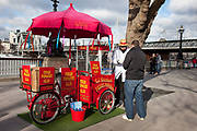 A walk along the River Thames on the Southbank in London. A popcorn seller serves a customer. This area is very popular especially on the weekends for Londoners to walk and see different arts, culture and entertainment.