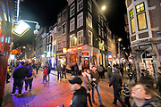 Nederland, Amsterdam, 5-3-2019Drukte in de Warmoestraat bij de Wallen. Toeristen lopen nieuwsgierig door de straat .The Netherlands, tourists visiting the redlight district, red, lightFOTO: FLIP FRANSSEN