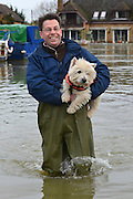 ***TODAY PICTURE***© Licensed to London News Pictures. 12/02/2014. Old Windsor, UK. Freddy a boat owner carries Foxy his dog through floodwater to dry land for a walk.  Flooding in OLD WINDSOR in Surrey today 12th February 2014 after the River Thames burst its banks. The Environment Agency has issued 14 Severe Flood Warnings alone the Thames. Photo credit : Stephen Simpson/LNP
