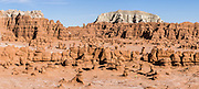 A boy in yellow shirt runs through a panorama of hoodoos in Goblin Valley State Park, in central Utah, USA. Admire fanciful hoodoos, mushroom shapes, and rock pinnacles in fascinating Goblin Valley State Park, in Emery County between the towns of Green River and Hanksville. The Goblin rocks eroded from Entrada Sandstone, which is comprised of alternating layers of sandstone (cross-bedded by former tides), siltstone, and shale debris which were eroded from former highlands and redeposited in beds on a former tidal flat. As part of the Colorado Plateau, the San Rafael Swell is a giant dome-shaped anticline of rock (160-175 million years old) that was pushed up during the Paleocene Laramide Orogeny 60-40 million years ago. Since then, infrequent but powerful flash floods have eroded the sedimentary rocks into valleys, canyons, gorges, mesas, and buttes. This panorama was stitched from 3 overlapping photos.