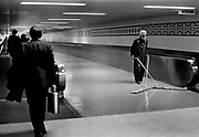 Cleaner and commuters on the moving walkways, Heathrow airport. In the 1950 the first Indians to arrive in Britain were Sikhs and there has been a tradition of employing Indians in Heathrow, mainly in service jobs. Terminal 3 was expanded with the addition of an arrivals building in 1970. Other new facilities included the UK's first moving walkways. Coming and Going is a project commissioned by the Museum of London for photographer Barry Lewis in 1976 to document the transport system as it is used by passengers and commuters using public transport by trains, tubes and buses in London, UK.