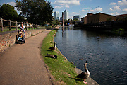 A mother pushes her child along the towpath of Regents Canal in East London. Canary Wharf financial district is in the background.