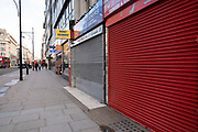 Shops with their shutters down on Oxford Street which is empty of shoppers as the national coronavirus lockdown three continues on 28th January 2021 in London, United Kingdom. Following the surge in cases over the Winter including a new UK variant of Covid-19, this nationwide lockdown advises all citizens to follow the message to stay at home, protect the NHS and save lives.