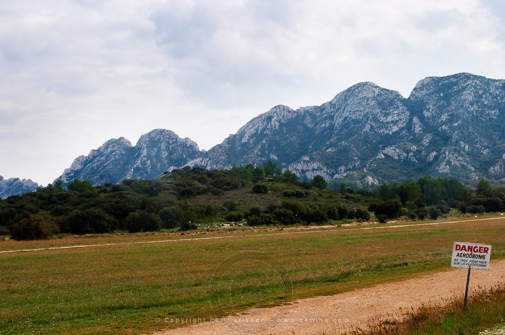 The Romanin air field with a sign saying danger aerodrome. In the background the Alpilles mountain range. Chateau Romanin, Saint Remy de Provence, Bouches du Rhone, Provence, France, Europe