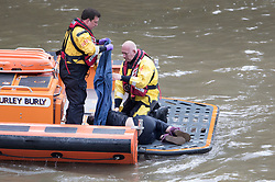 © Licensed to London News Pictures. 29/03/2017. London, UK. An RNLI crew attend to a person they rescued from the River Thames under Westminster Bridge. This is the second person who has jumped in to the River from Westminster bridge in the space of two hours. Police are still searching for the first person. Photo credit: Peter Macdiarmid/LNP
