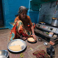 Woman preparing chapati at her kitchen