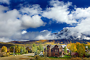 SHOT 9/27/12 11:22:02 AM - A view of houses in the town of Crested Butte, Co. and Mount Crested Butte from the Lower Loop Trail in Crested Butte, Co. as aspen trees change colors as the fall foliage season comes to a peak in Colorado. Populus tremuloides, the Quaking Aspen or Trembling Aspen, is a deciduous tree native to cooler areas of North America and is generally found at 5,000-12,000 feet. The name references the quaking or trembling of the leaves that occurs in even a slight breeze due to the flattened petioles. It propagates itself by both seed and root sprouts, and extensive clonal colonies are common. Each colony is its own clone, and all trees in the clone have identical characteristics and share a root structure. (Photo by Marc Piscotty / © 2012)