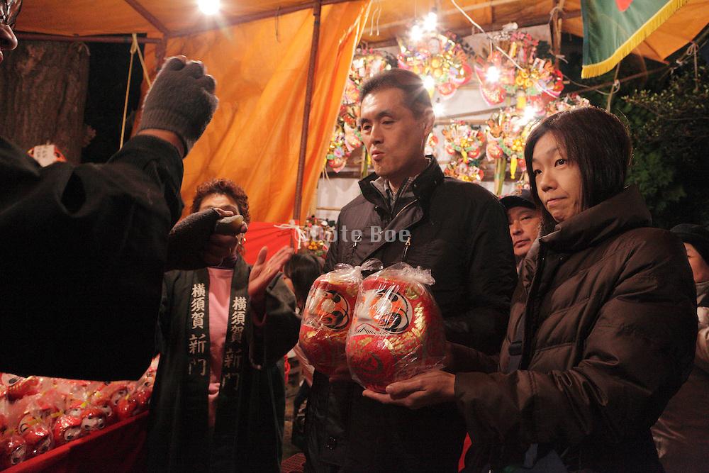 Japanese couple buying a Daruma at a Torino no Ichi fair
