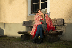 Young couple wrapped in a blanket and sitting on bench during sunset, Munich, Bavaria, Germany