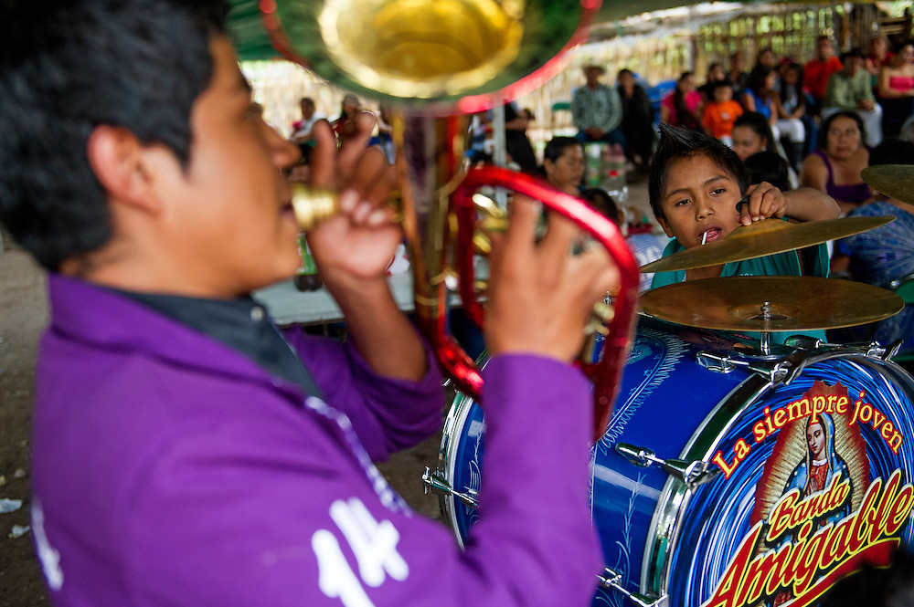 """In this July 23, 2016 photo, a member of """"La siempre joven Banda Amigable"""" sucks on a lollipop as he operates the drum cymbals during a wedding reception in Santa Ana, in the Mexican state of Oaxaca. The band, whose name translates to """"The Forever Young Friendly Band,"""" was aptly named to play for the wedding reception celebrating 75-year-old Pablo Ibarra and his 65-year-old bride, Francisca Santiago, finally married in the church after nearly five decades together. NICK WAGNER / ASSOCIATED PRESS"""
