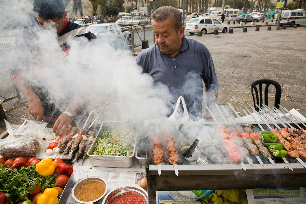 A man grills meat at a stall on Salah ad Din Street in Jerusalem, Israel.