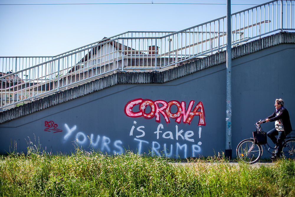 """Graffiti sprayed on a wall at the Oberursel-Stierstadt S-Bahn station reads: 'Corona is Fake'. and somebody added later """"Yours Trump""""."""
