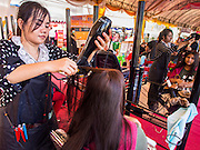"""24 JULY 2014 - BANGKOK, THAILAND:  A woman gets her hair done for free at the happiness party in Bangkok. The Thai Junta is organizing a series of public events throughout Thailand meant to bolster public opinion. The events are called """"restoring happiness to the people"""" parties. They feature historic pageants, music, food, health checks and free haircuts. The party in Bangkok is on Sanam Luang, the Royal Parade Ground, which is near the Grand Palace and the Ministry of Defense.   PHOTO BY JACK KURTZ"""