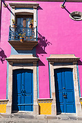The brightly painted pink Hotel Centenario Centro with blue doors in the beautiful colonial village of Bernal, Queretaro, Mexico. Bernal is a quaint colonial town known for the Pena de Bernal, a giant monolith which dominates the tiny village is the third highest on the planet.