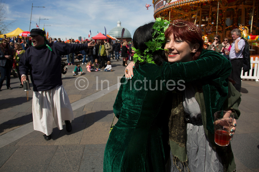 May Day custom of Deptford Jack in the Green, a man encased in a framework entirely covered with greenery, is one of the lesser-known modern revivals by the Blackheath Morris Men of English traditional customs on May 1st 2016 in London, United Kingdom. An embrace for one of the May Queens. Fowlers Troop Jack in the Green was revived in the early 1980s. Originally a revival from about 1906, it developed from the 17th Century custom of milkmaids going out on May Day with the utensils of their trade, decorated with garlands of flowers and piled into a pyramid which they carried on their heads. By the mid eighteenth century other groups, notably chimney sweeps, were moving in on the milkmaids territory as they saw May Day as a good opportunity to collect money, so carried a Jack in the Green. Over the last 25 years several popular festivals have grown up around the Jack in the Green tradition. Deptford Jack in the Green is not very widely known although it has been running since the early 1980s.