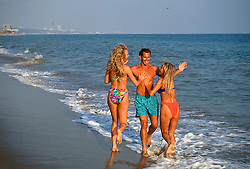 Man Being Playfully Attacked By Two Blonde girls At The Beach In California