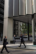 Financial industry people walk through reflected light from a nearby skyscraper in the City of London, the capitals financial district aka the Square Mile, on 17th May 2018, in London, UK.