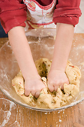 Girl kneading dough in bowl for cookies