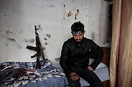 A Free Syrian Army soldier sits on the bed of a house in the village of Adthar, Idlib province, Syria. 19/11/2012