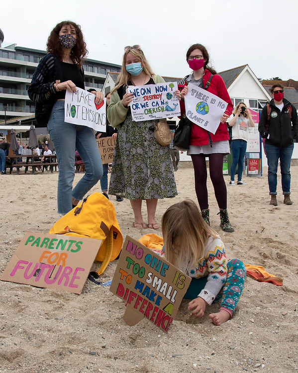 """A small child plays on the beach in front of a sign that reads """"no one is too small to make a difference"""" as part of the youth climate strike in Crornwall, happening as the G7 summit begins. 11th June 2021. Anna Hatfield/Pathos"""