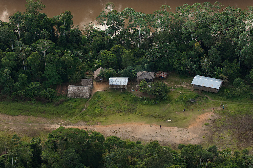 Huaorani Houses seen from the air. They are simple structures built directly on the ground. The frame is made from thin branches which is then covered with palm leaves. They are just abandoned or burnt down when the family move to a different area.<br /> Bameno Community. Yasuni National Park.<br /> Amazon rainforest, ECUADOR.  South America<br /> This Indian tribe were basically uncontacted until 1956 when missionaries from the Summer Institute of Linguistics made contact with them. However there are still some groups from the tribe that remain uncontacted.  They are known as the Tagaeri & Taromenane. Traditionally these Indians were very hostile and killed many people who tried to enter into their territory. Their territory is in the Yasuni National Park which is now also being exploited for oil.