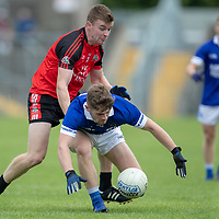 Cratloe's Rian Considine falls after a tackle from Clondegad's Tony Kelly