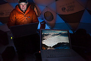 Ian Howat, a glaciologist with Ohio State University, works up GPS-derived ice velocity data on his laptop while Ethan Welty reviews images pulled from a timelapse camera inside the basecamp tent at the Columbia Glacier, near Valdez, Alaska.