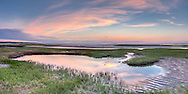 Sunset clouds reflect in a tide pool at Paine's Creek Beach in Brewster.
