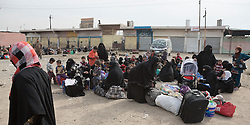 Licensed to London News Pictures. 10/11/2016. Mosul, Iraq. Women and children, escaping from areas within Mosul where fighting between Iraqi Security Forces and Islamic State militants are fighting, sit as they wait to board a bus in the city's Gogjali District. The bus, provided by the Iraqi Army, will take them to the safety of a refugee camp in Iraqi-Kurdistan.<br /> <br /> The battle to retake Mosul, which fell June 2014, started on the 16th of October 2016 with Iraqi Security Forces eventually reaching the city on the 1st of November. Since then elements of the Iraq Army and Police have succeeded in pushing into the city and retaking several neighbourhoods allowing civilians living there to be evacuated - though many more remain trapped within Mosul. Photo credit: Matt Cetti-Roberts/LNP