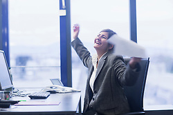 Excited businesswoman celebrating her success in an office, Freiburg Im Breisgau, Baden-Württemberg, Germany