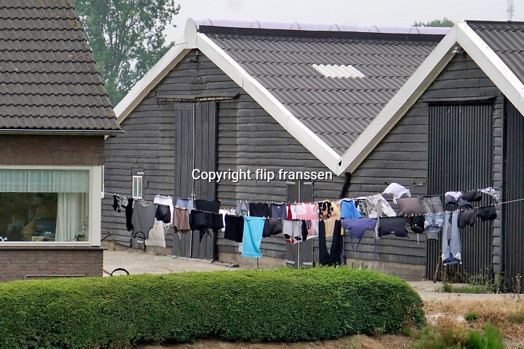 Nederland, Batenburg, 28-7-2019Wasgoed hangt aan lijnen te drogen tussen de schuren en het woonhuis van een boerderij ..Foto: Flip Franssen