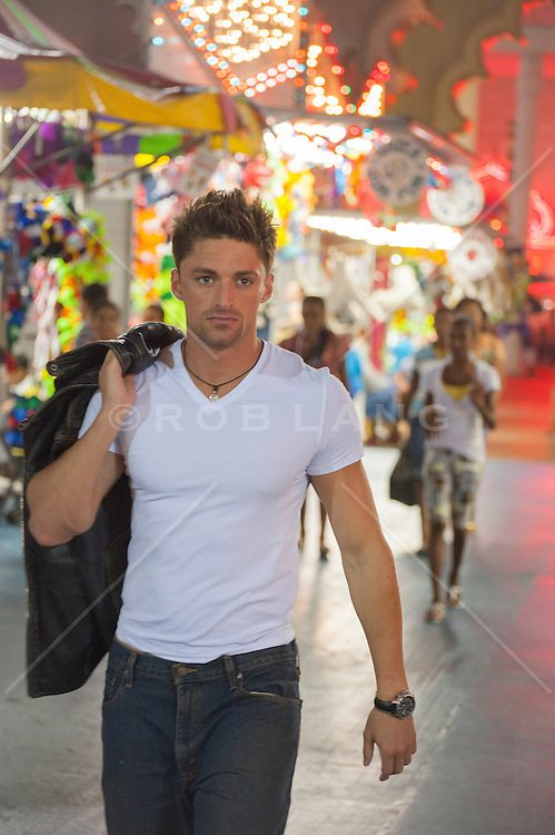 good looking twenty something year old man walking through a carnival in Atlantic City, New Jersey