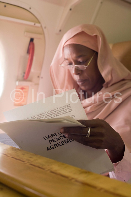 Dr Safaa Elagib Adam reads documents on the journey by air to the firstever international Conference on Womens' Challenge in Darfur. Seated in a chartered Russian Antonov aircraft during flight to Al Fasher (also spelled, Al-Fashir) where women from remote parts of Sudan gathered to discuss peace and political issues. The short flight saves her a hazardous five-day drive by road, known for extreme acts of violence by rebels and Janjaweed soldiers. The Sudanese Women General Union has 27,000 branches all over Sudan, including Darfur. They have representatives in all rural villages, across communities of around 80 tribes and clans. The women of Sudan are wives, mothers, farmers a real force and historically, there have been female leaders.