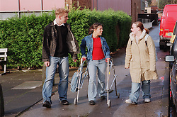 Teenage girl with physical disability using walking frame to walk along street with college friends,