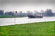 Nederland, Mook, 9-2-2020 Het water in de Maas in Noord Limburg staat hoog. Uiterwaarden lopen op sommige plekken onder en de veerpont tussen Cuyk en Middelaar is uit de vaart. Er zijn ook enkele recent voltooide hoogwater projecten in werking. Zo worden kleine beekjes en stroompjes in het gebied afgesloten om te voorkomen dat het maaswater naar het binnenland vloeit. een binnenvaartschip vaart stroomopwaarts .Foto: Flip Franssen