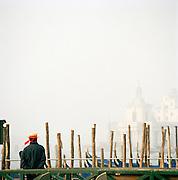A gondolier waiting by his gondola, Venice, Italy