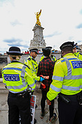 """Police arrested an Animal and climate activist from Animal Rebellion after they dyed blood-red Buckingham Palace fountains on Thursday, Aug 26, 2021 - signifying as their statement said """"its' demonstrable role in hunting and animal agriculture"""". (VX Photo/ Vudi Xhymshiti)"""