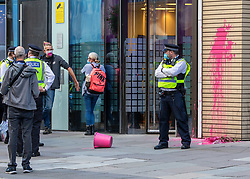 © Licensed to London News Pictures. 10/09/2020. London, UK. A police officer stands next to pink paint that was splattered at the Dept of Health during a demo by campaigning group Burning Pink. A large police presence outside the Department of Health in Victoria Street in Westminster after protestors calling themselves Burning Pink a campaigning group splatters pink paint at the entrance of the Government offices and then glues themselves to one of the front window panes this morning. Photo credit: Alex Lentati/LNP