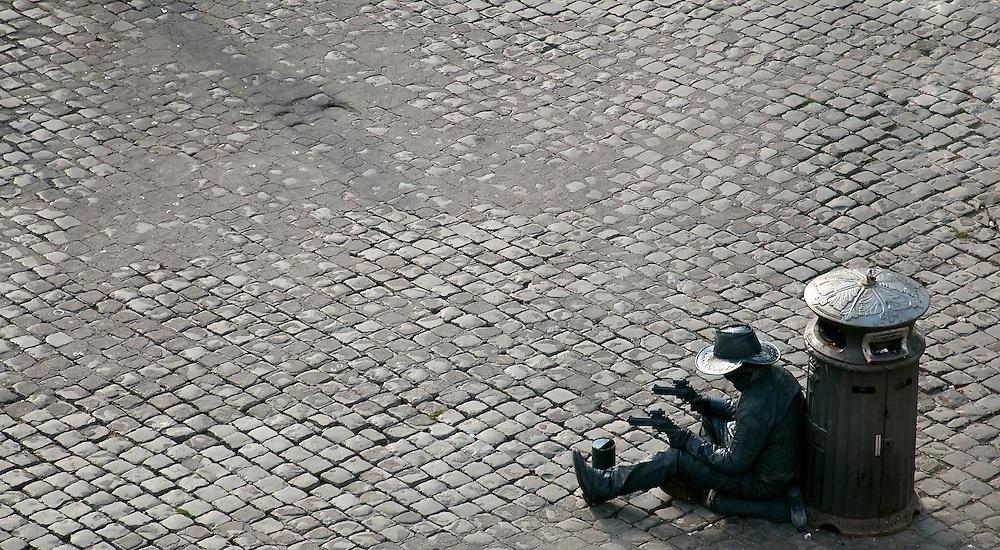 A cowboy street artist taking a break next to a bin.