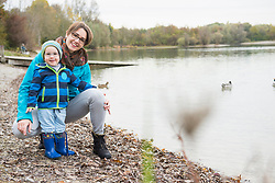 Portrait of mother with son standing at shore of lake