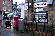 People walk past Covid-19 test posters outside a pharmacy in three different languages placed in the community noticeboard in Wapping, Tower Hamlets on 30th January 2021 in London, United Kingdom. The posters, in Somali, English and Bangladeshi point the way to find a coronavirus test centre if symptoms are occurring.
