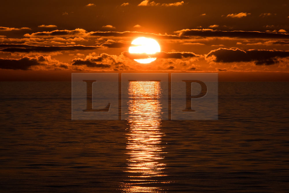 © Licensed to London News Pictures. 05/12/2016. Wick, UK.  Sunrise over the calm and glassy sea in the Moray Firth in Scotland this morning, 5th December 2016. The weather is set to be bright but cold in northern parts of the UK today, with milder weather forecast later in the week. Photo credit: Rob Arnold/LNP
