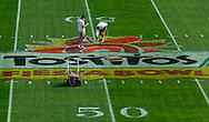 MORNING JOURNAL/DAVID RICHARD.Workers at Sun Devil Stadium in Tempe, AZ. paint the midfield logo yesterday while preparing for Monday's Fiesta Bowl pitting Ohio State against Notre Dame.